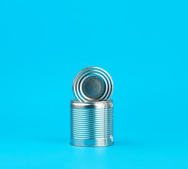 open hard iron can for food preservation on a blue background,