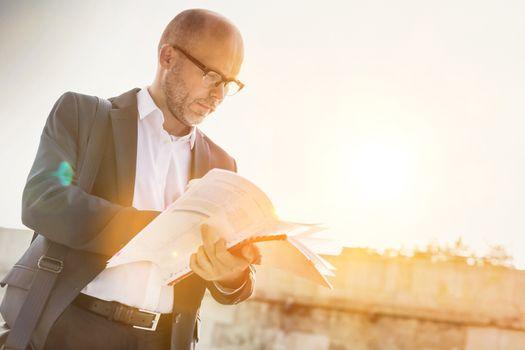 Portrait of businessman reading documents