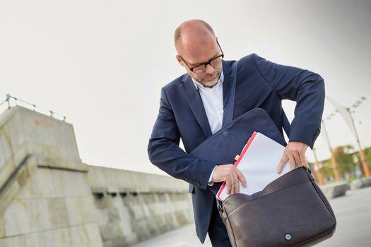 Portrait of mature businessman putting paperwork on his bag