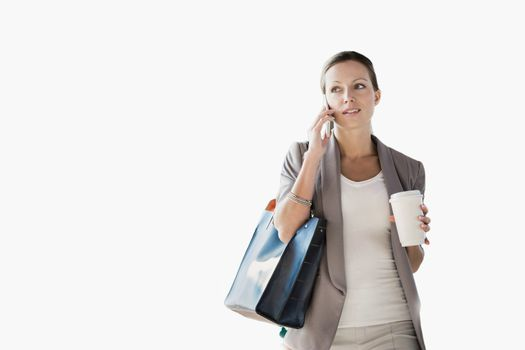 Cutout of businesswoman talking on smartphone while drinking coffee