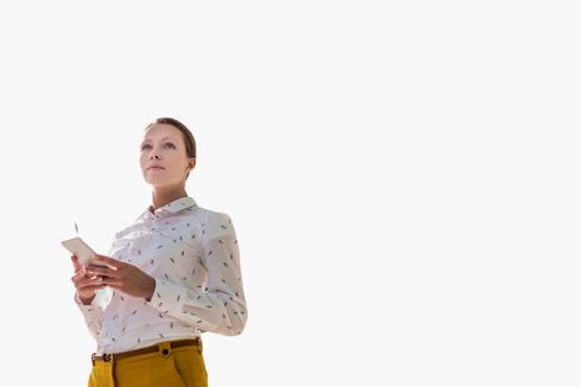 Cutout of young attractive businesswoman standing while using smartphone