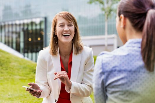 Businesswoman laughing while talking to her colleague