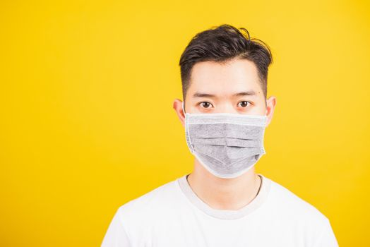 Closeup Asian young man wearing face mask protective germ virus or air dust, studio shot isolated on yellow background and copy space, medical outbreak coronavirus COVID-19 concept