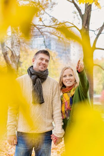 Mature couple enjoying autumn while walking in park in park