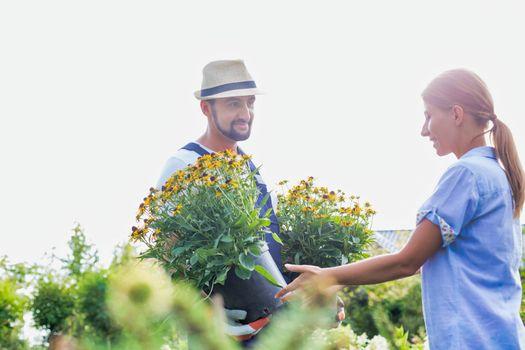 Portrait of mature gardener showing flowers to woman buyer in shop