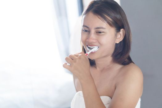 Closeup woman brushing teeth in the bathroom, health care concept