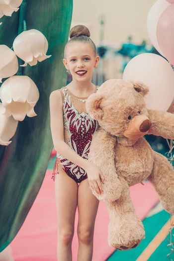 Little gymnast with her sports awards and big teddy bear on the carpet in rhythmic gymnastics