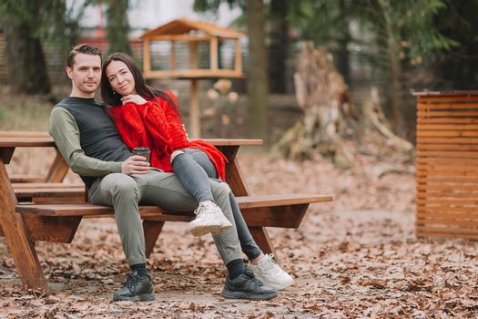 Young couple in the park outdoors at an authentic table in a cafe