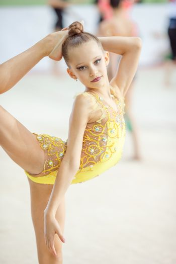 Portrait of beautiful little gymnast girl with her performance on the carpet on the competition