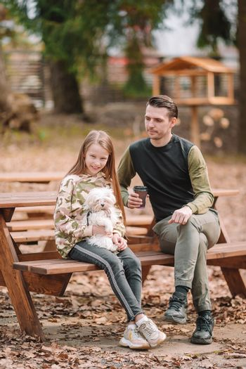 Adorable little girl and young father with puppy outdoor