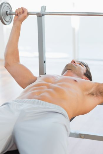 Shirtless fit man lifting the barbell bench press