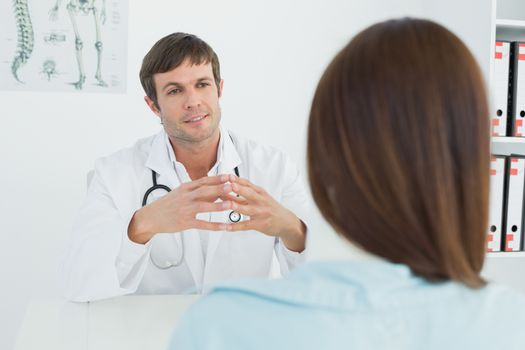 Doctor listening to patient with concentration in medical office