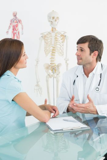 Male doctor listening to patient with concentration at desk
