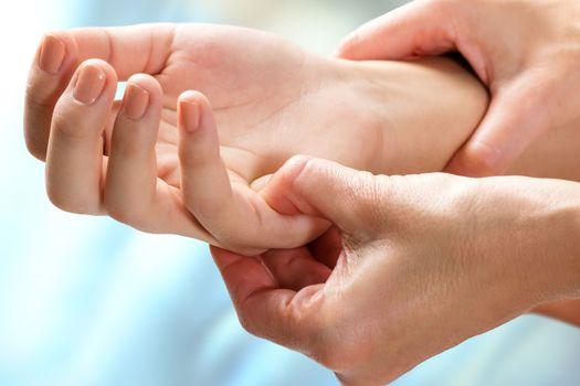 Therapist manipulating sensitive area on hand.