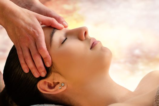 Massage therapist touching sensitive area between eyes on woman.