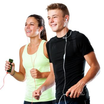 Close up portrait of active teen couple doing fitness workout together.Couple jogging together with smart phones and earphones isolated on white background.