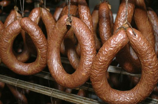 Smoked sausages hanging on a metal frame in the smokehouse.