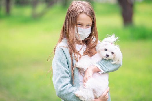 Little girl wearing a protective mask is walking alone with a dog outdoors because of the coronavirus pandemic