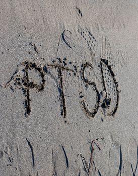 ptsd text on a beach sand, mental health concept