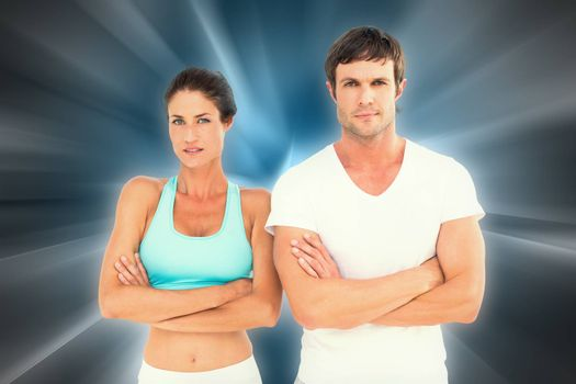 Portrait of a fit young couple with arms crossed against abstract background