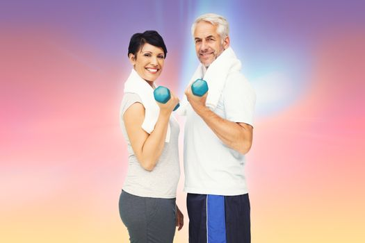 Portrait of a fit mature couple exercising with dumbbells against abstract background