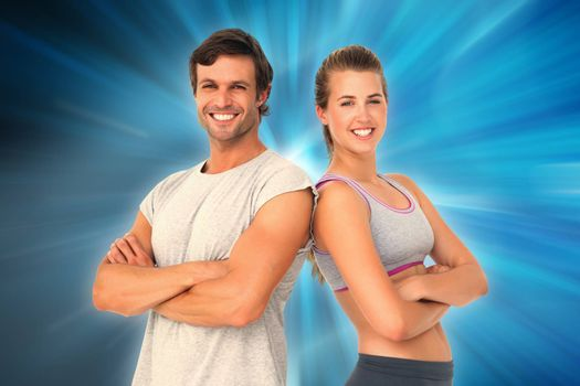 Portrait of a sporty young couple with arms crossed against abstract background