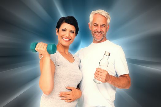 Happy fit couple with dumbbell and water bottle against abstract background