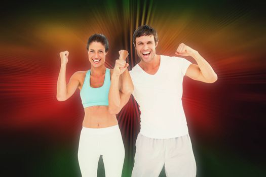 Cheerful fit couple clenching fists against abstract background