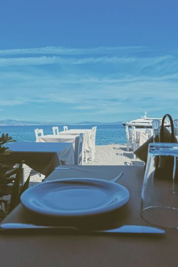 Empty restaurant by the Aegean sea and cruise boat, travel and nature, scene