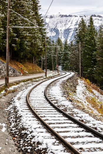 Old railways on edge of mountain in pine woods of Switzerland covered by snow in winter.