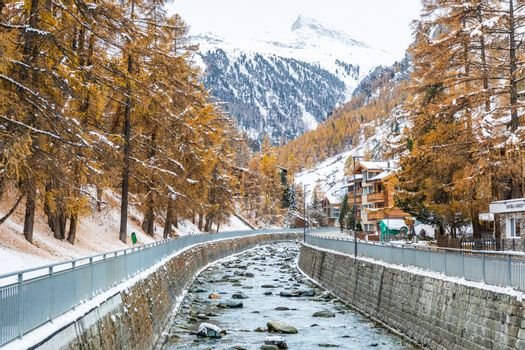Landscape of rocky stream alongside wooden houses and resorts in Zermatt, Switzerland, environment covered by snow in winter.