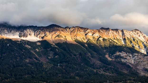Mountain range with shining sunlight in morning of cloudy day, Innsbruck, Austria.