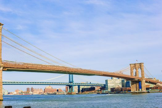 Brooklyn Bridge over river viewed from New York City.