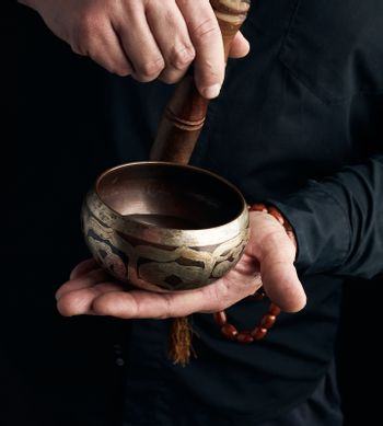 man in a black shirt rotates a wooden stick around a copper Tibetan bowl. ritual of meditation, prayers and immersion in a trance. Alternative treatment