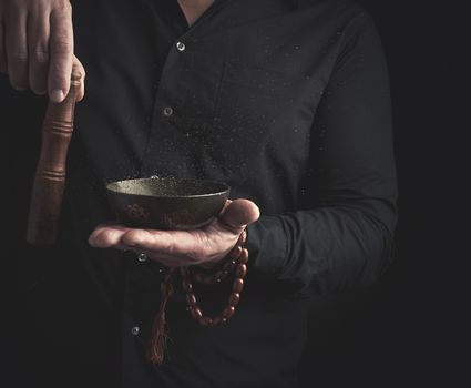 man in a black shirt rotates a wooden stick around a copper Tibetan bowl of water. ritual of meditation, prayers and immersion in a trance. Alternative treatment
