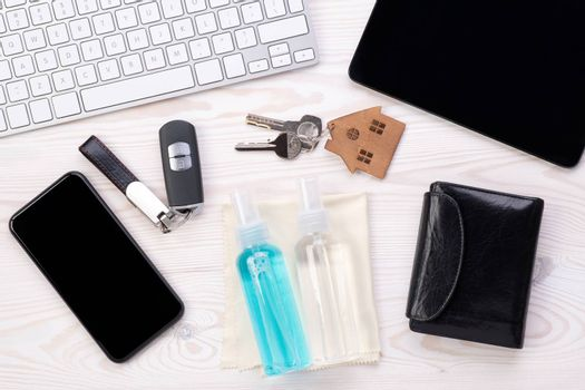 Everyday objects that need to be regularly cleaned with an antiseptic such as phone, computer keyboard, wallet and keys on a desk, top view