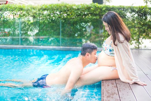 Asian pregnant woman. Mom and newborn baby. Mother day and International women day. Relax and recreation with husband at swimming pool.