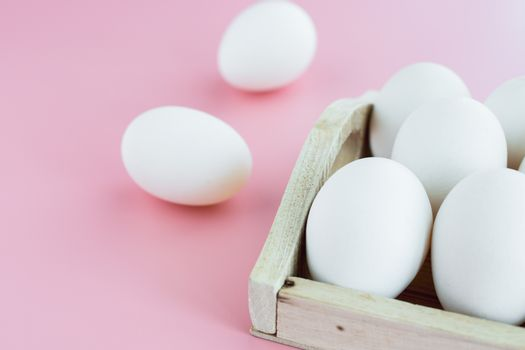 White eggs in the wooden tray on pink background for healthy food concept