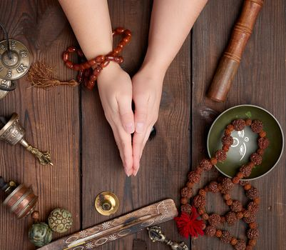 two hands in a prayer pose on a wooden brown table in the middle of vintage Tibetan meditation tools, alternative medicine, top view