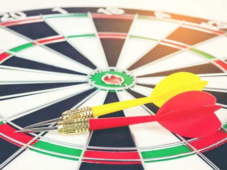 Red and yellow Dart arrows and dartboard with light