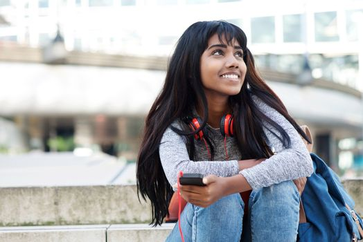young Indian woman sitting on steps with mobile phone and looking away