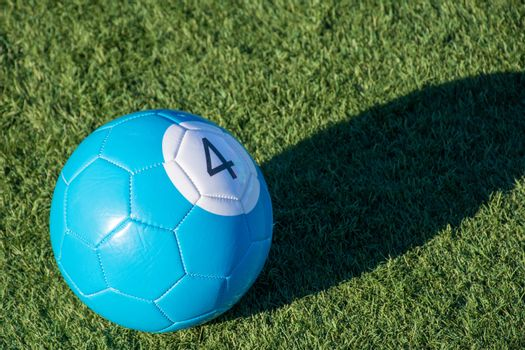Blue number 4 soccer billiards or pool ball on green grass with a shadow and copy space. Concept of sports, recreation and childhood fun.