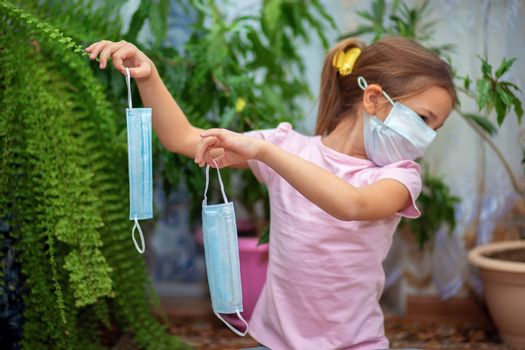 A little girl in a medical mask holds two more masks in her hands. Maximum protection during quarantine