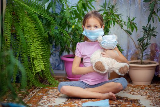 The girl put on a medical mask on herself and on her toy - a teddy bear. Quarantine and self-isolation during the epidemic of the virus