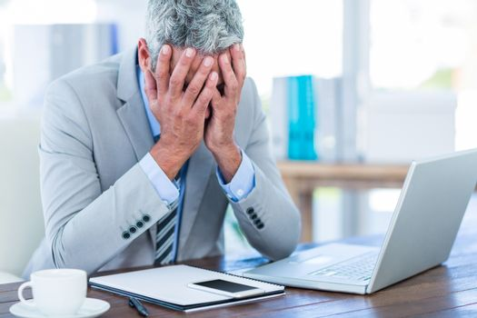 Depressed businessman with hands on head