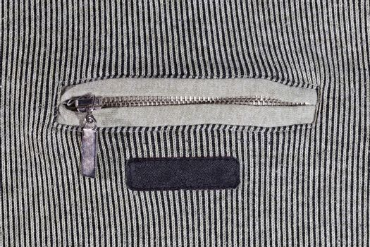abstract vertical striped texture of flat fabric surface with zip locking chest pocket, and black blank label.