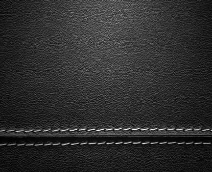 Real close-up of black leather background texture with horizontal stitch.