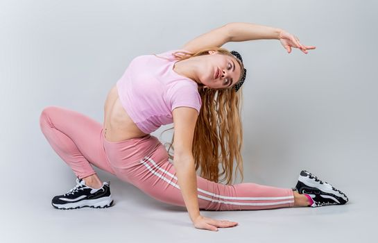 Fitness, sport, training and lifestyle concept. Athletic acrobat woman wearing pink sportswear stretching in the studio isolated on gray background