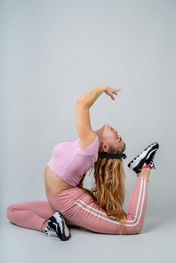 Fitness, sport, training and lifestyle concept. Acrobat woman wearing pink sportswear working out in the studio isolated on gray background with copy space