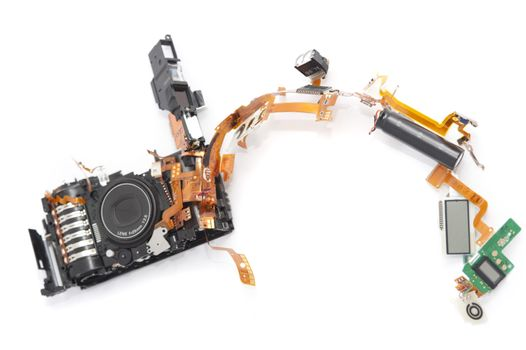 Dismantled camera lying in parts on white